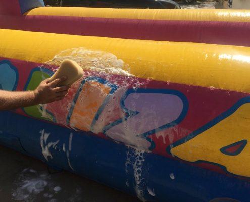 Limpiando un hinchable... parte de la higiene en fiestas infantiles.